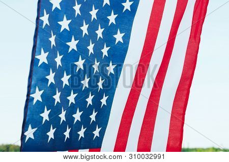 Flag Of The United States Of America Fluttering In The Wind Against The Blue Skyy Close Up