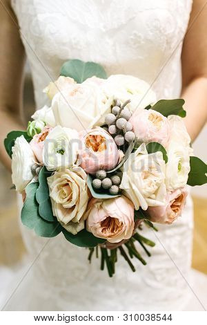 A Bride In A White Dress Is Holding A Beautiful Wedding Bouquet. Fresh Flowers, Including Peony Rose