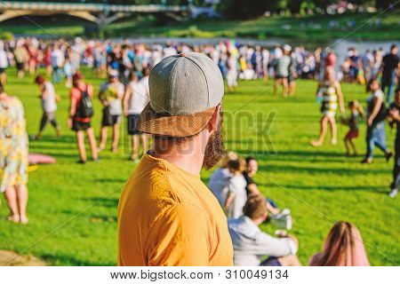 poster of Hipster in cap happy celebrate event fest or festival. Summer fest. Man bearded hipster in front of crowd. Open air concert. Fan zone. Music festival. Entertainment concept. Visit summer festival