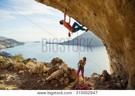 Young Man Starts Climbing Challenging Route In Cave, His Female Partner Belaying Him. With Beautiful