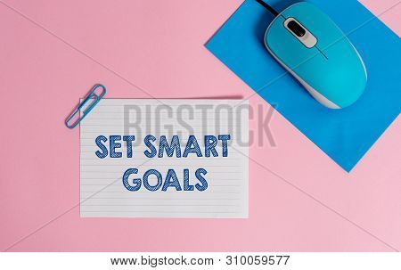 Text sign showing Set Smart Goals. Conceptual photo giving criteria to guide in the setting of objectives Wire electronic mouse striped blank paper sheets clip colored background. poster