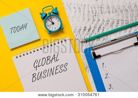Conceptual hand writing showing Global Business. Business photo showcasing Trade and business system a company doing across the world Spiral notepad sheet marker alarm clock wooden background. poster