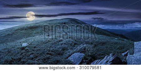 Beautiful Panorama In Mountains At Night In Full Moon Light. Rocks On The Grassy Slope. Cloud Above