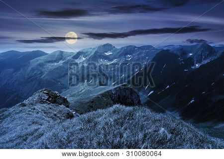 Beautiful Landscape Of Fagaras Mountains At Night In Full Moon Light. Rocks On Steep Grassy Slopes.