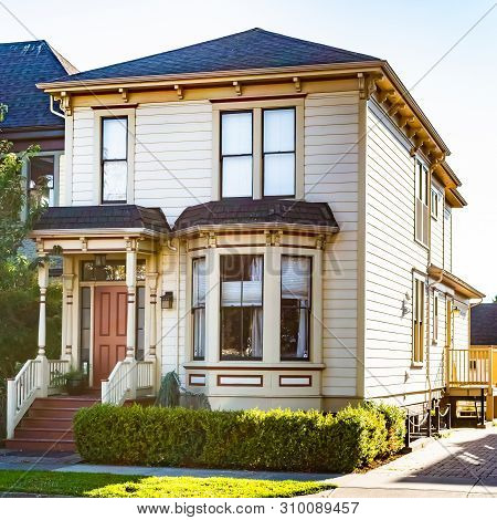 Semi detached two storey/ double floor townhouse with front porch in Victoria, Canada. Single family house/home. Real estate architecture. poster