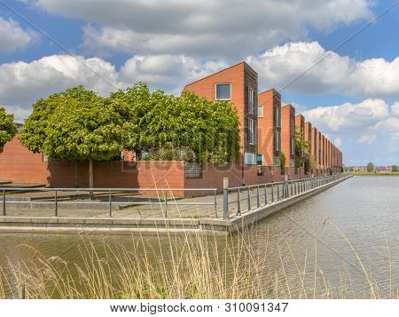 Modern detached family houses adjecent to water edge in suburb in Groningen Netherlands poster