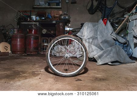 Dirty Bicycle Wheel On The Floor Of A Messy Home Garage With Equipment, Workbench, Tools And Cloth I