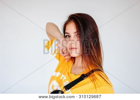 Portrait Of Tipical Thoughtful Teenager Girl With Dark Long Hair In Yellow T-shirt On The Grey Backg