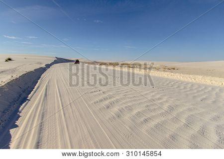 Car Driving Through Desert. Single Car Drives Down A Rough Washboard Dirt Road Through A Remote Dese