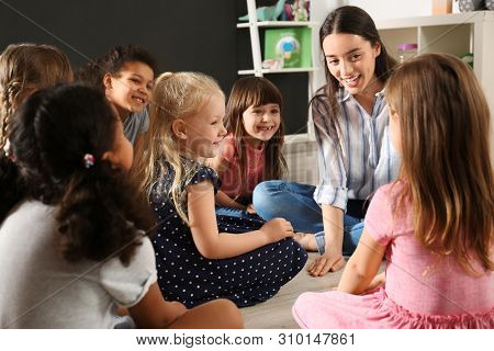Cute Little Children With Nursery Teacher In Kindergarten. Indoor Activity