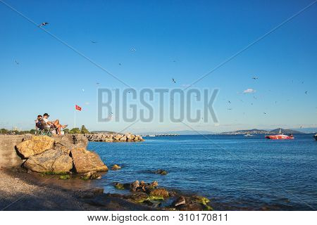 Istanbul, Turkey: View Of Two Resting Friends At Beach Of The Marmara Sea In Sunny Summer Day Locate