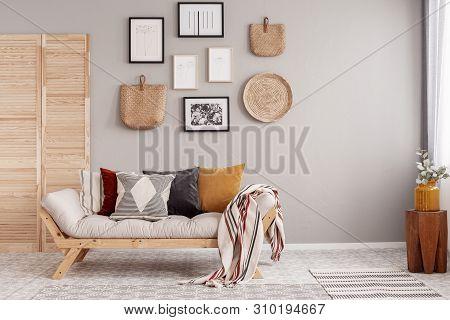 Flowers In Yellow Vase On Wooden Stool In Beige Scandinavian Living Room Interior