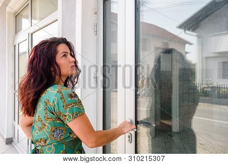 Aluminum Door. Young Woman Holds Doorknob On Aluminum Door