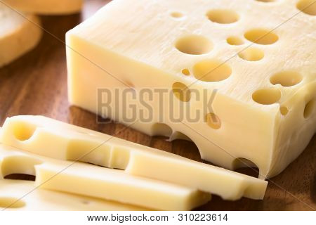 Piece Of Emmental, Emmentaler Or Emmenthal Cheese On Wooden Plate (selective Focus, Focus One Third