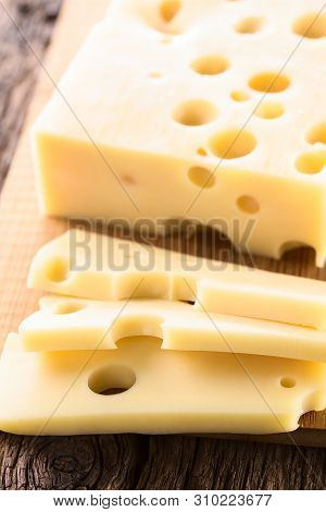 Piece And Slices Of Emmental, Emmentaler Or Emmenthal Cheese On Wooden Cutting Board (selective Focu