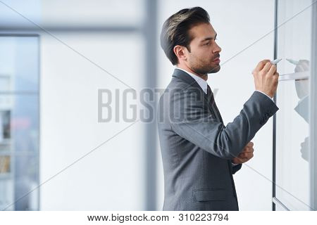 Young elegant teacher writing down points of the subject