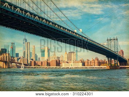 The Manhattan Bridge with Manhattan in the background at the day-time, New York City, United States. Photo in retro style. Added paper texture.