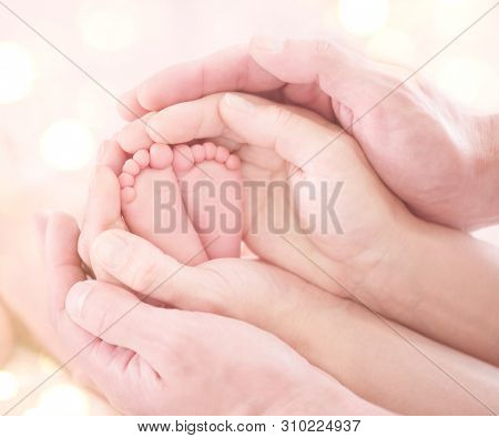 Baby feet in mother and father hands. Tiny Newborn Baby's feet on hands closeup. Mom, Dad and Child together. Healthy and Happy Family concept. Parents. Beautiful photo of Parenthood, adoption