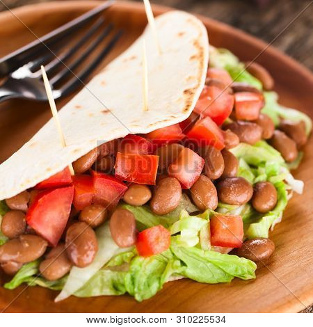 Fresh Homemade Vegan Tacos Made Of Folded Flour Tortilla Stuffed With Lettuce, Cooked Beans And Toma