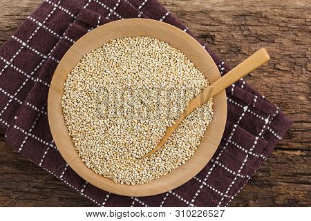 Raw White Quinoa Seeds (lat. Chenopodium Quinoa) On Wooden Plate With Wooden Spoon, Photographed Ove