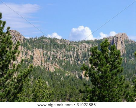 View Of The Rock Formations In The Mountains With Pine Trees In The Foreground Seen Along Needles Hi