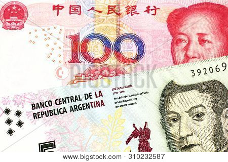 A five peso bill from Argentina, close up in macro with a red, one hundred yuan Chinese renminbi bank note poster