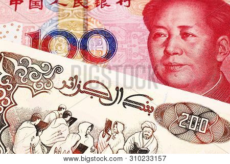 A beige, two hundred Algerian dinar bill with a red, Chinese renminbi one hundred yuan bank note close up in macro poster
