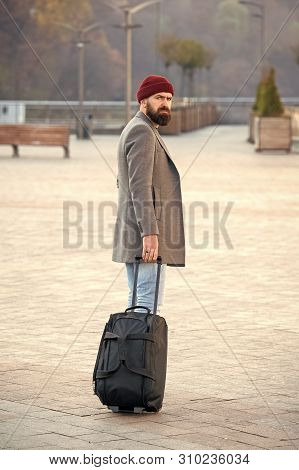 poster of Hipster ready enjoy travel. Carry travel bag. Man bearded hipster travel with luggage bag on wheels. Adjust living in new city. Traveler with suitcase arrive airport railway station urban background.