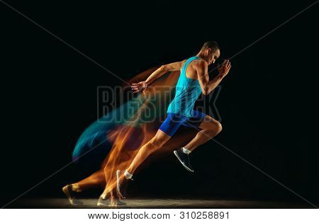 Professional Male Runner Training Isolated On Black Studio Background In Mixed Light. Man In Sportsu