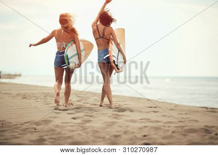 Surfers on beach having fun in summer. Surfer women with surf board smiling on beach