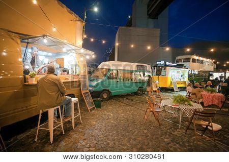 Lisbon, Portugal: Fast Food Trucks Parked At Urban Area And Hungry People Having Late Dinner Outdoor