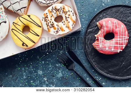 Pink Frosted Donut With Bite Missing On A Plate With Assortment Donuts Box On Dark Background. Top V