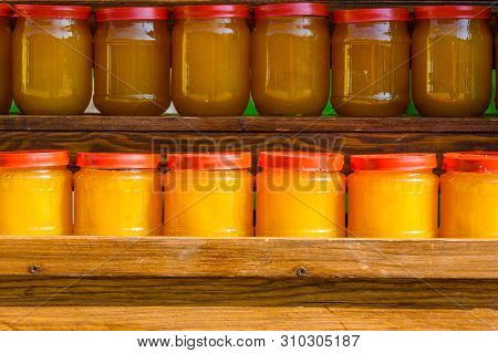 Background Of Many Glass Jars With Honey