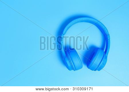 Blue Headphones, Top View Of Headphones On Blue Background. Minimalist Photo Of Earphones With Copy