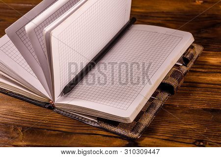 Opened Notepad And Pencil On Rustic Wooden Table