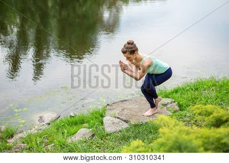 Young Beautiful Caucasian Brunette Girl Doing Yoga On A Green Lawn Against The Background Of The Riv