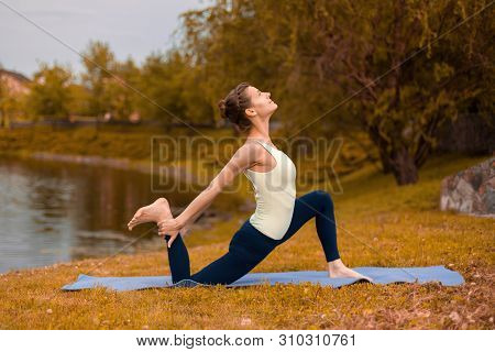 Slim Brunette Girl Goes In For Sports And Performs Yoga Poses In The Fall In Nature By The Lake.