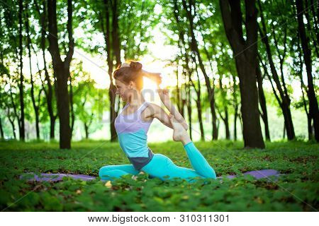 Thin Brunette Girl Doing Mermaid Exercise, Eka Pada Rajakapotasana Pose In A Summer Park On A Sunset
