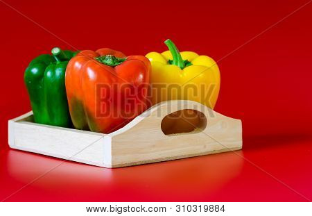 Summer Of Sweet Bell Pepper In Wood Box On Red Background.
