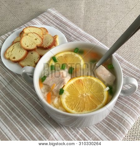 Delicious Chicken Soup With Lemon, Rise, Carrot, Green Onion And Bread Sticks Aside. Soup Cup With A