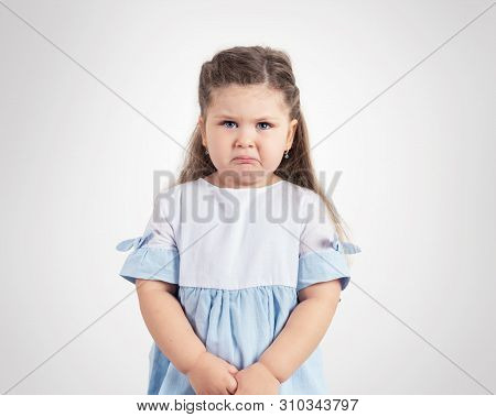 Portrait Of Crying Little Girl On Grey Background.