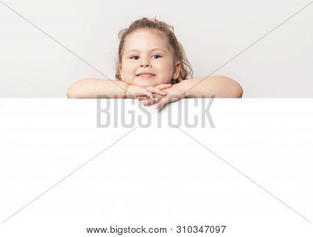 Smiling Blue Eyed Little Girl Peeking Behind A White Board.