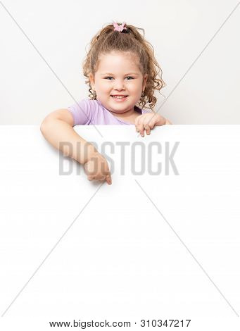 Smiling Blue Eyed Little Girl Peeking Behind A White Board.