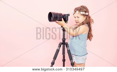 Little Girl Holding Camera And Smiling On Pink Background.