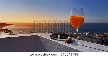 Glass Of Fresh Orange Juice And Sea View From Penthouse Terrace In Albufeira, Algarve, Portugal