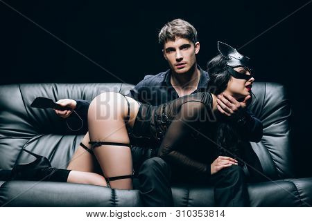 Passionate Man Sitting With Leather Spanking Paddle Near Sexy Woman In Bdsm Costume On Leather Sofa