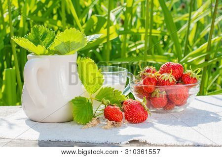 Strawberry Berries And Leaves, A Bowl Of Strawberries, A Jug And A Cup Of Milk On A Napkin On A Wood