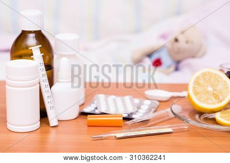 Medicines On The Table On The Background Of A Children's Bed With A Soft Toy