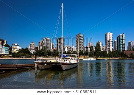 Cruising Catamaran Moored At False Creek Wharf In Downtown Of Vancouver City, The Beach And Resident