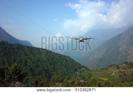 Lukla, Nepal - May 8, 2019: Small propeller airplane approaching Tenzing–Hillary Airport on background of green Himalaya Mountains